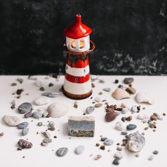Un petit phare décoratif avec des coquillages et des cailloux vacances d'été et concept de vacances
