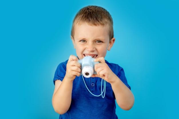 Petit photographe avec appareil photo jouet sur mur bleu.