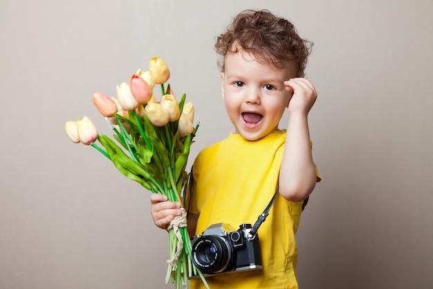 Petit photographe, un enfant avec un appareil photo dans les mains et des fleurs.