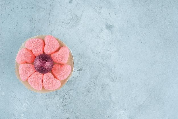Petit plat de confitures autour d'une boule décorative sur marbre.