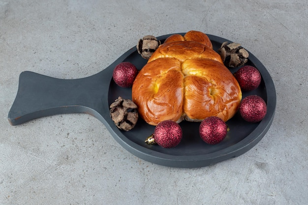 Petit plat de service avec un petit pain sucré sur une table en marbre.