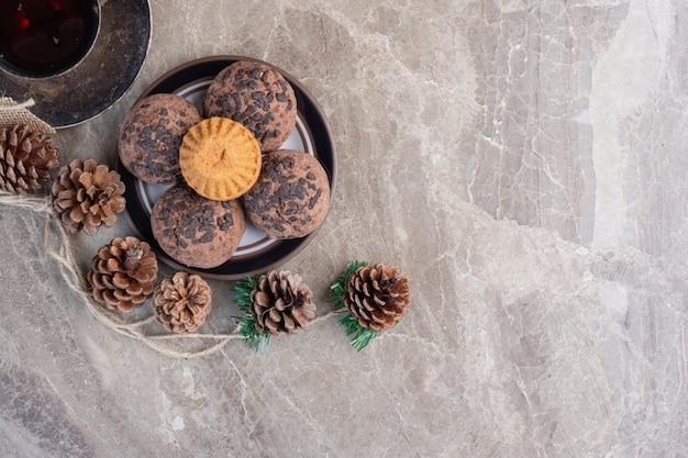 Petit plateau de biscuits, tasse de thé, paquet de pommes de pin et une couronne sur marbre.