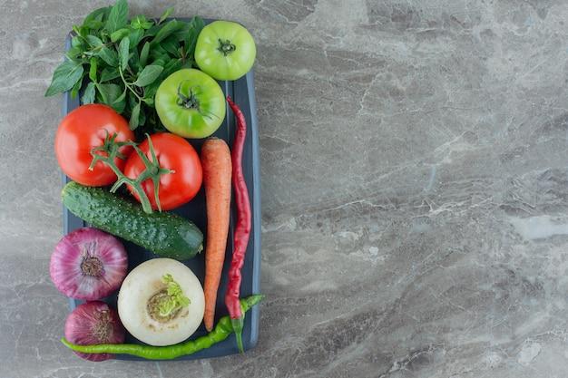 Petit plateau de concombre, carotte, tomates rouges et vertes, navet blanc, poivrons verts et rouges, oignons rouges et menthe sur marbre.