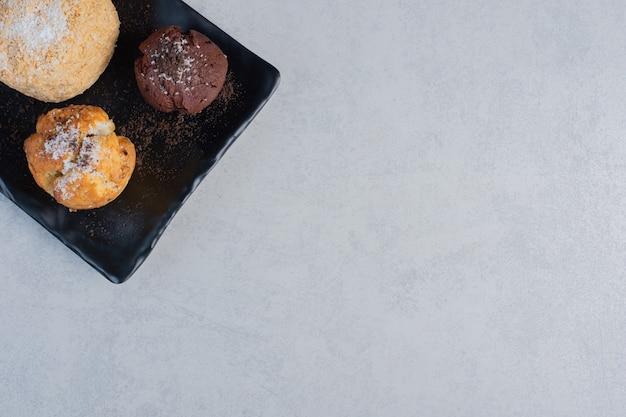 Petit plateau avec divers petits gâteaux sur une surface en marbre