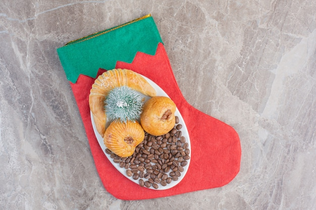 Petit plateau de pâtisserie festif sur une chaussette de noël sur marbre.