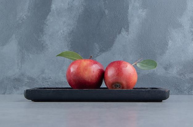 Un petit plateau avec des pommes juteuses sur marbre