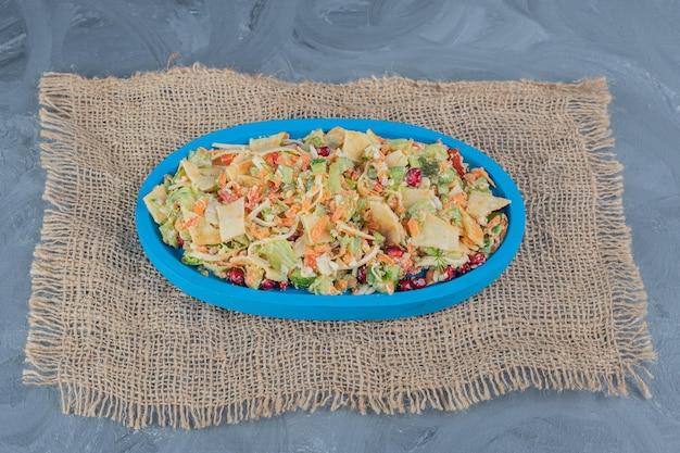 Petit plateau de salade de légumes mixtes sur table en marbre.