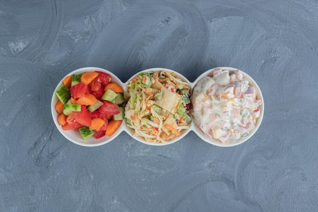Petit plateau de service avec des portions d'olivier de berger et salades de légumes mixtes sur fond de marbre.