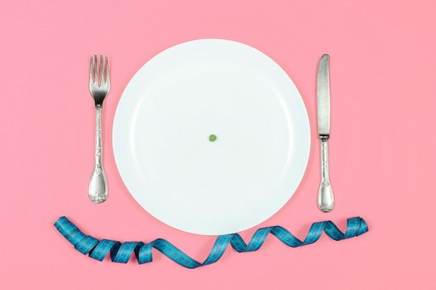 Un petit pois dans une grande assiette blanche avec un couteau, une fourchette et un ruban à mesurer sur fond rose