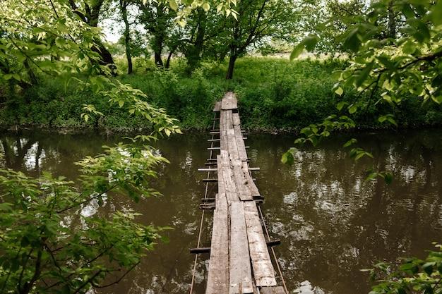 Un petit pont de bois sur un ruisseau doux dans un parc verdoyant.