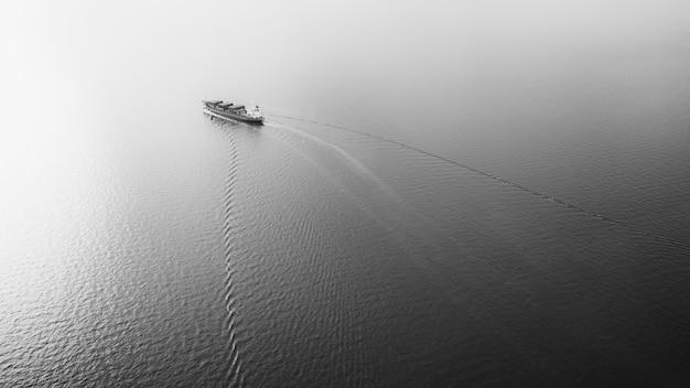 Petit porte-conteneurs noir et blanc naviguant en vue aérienne de la mer
