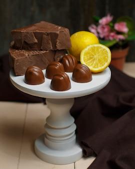 Petit porte-gâteaux blanc avec des chocolats au lait et du citron sur le dessus