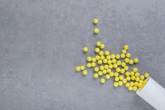 Un petit pot blanc de pilules d'acide ascorbique sur une surface grise