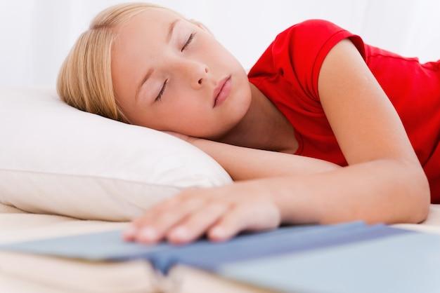 Petit rat de bibliothèque. petite fille mignonne dormant en position couchée dans son lit et tenant la main sur le livre