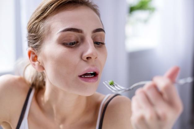 Petit repas. femme pâle triste tenant un pendant tout en mangeant un pois