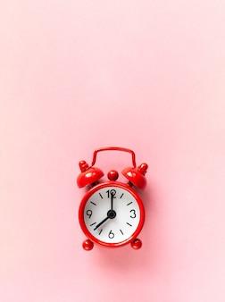 Petit réveil rouge sur fond rose pastel