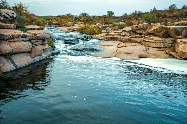 Un petit ruisseau brillant coule parmi les pierres lisses humides et sombres et les arbres bas et secs