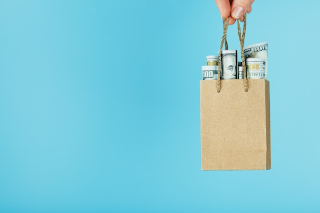 Un petit sac d'aide en papier dans une main tendue avec des dollars américains sur fond bleu. disposition du modèle d'emballage avec un espace pour la copie, la publicité.