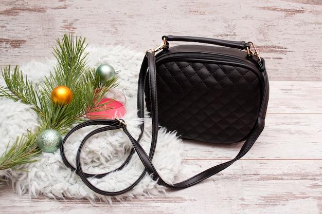 Petit sac à main féminin noir, branche de sapin avec ornements, bougie. concept de mode