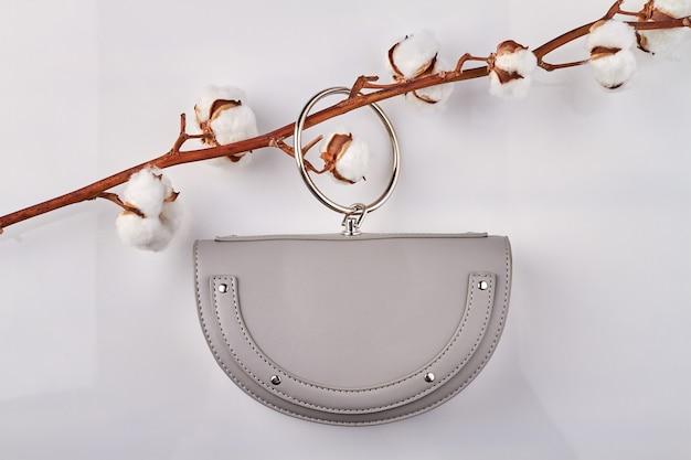 Petit sac à main lilas suspendu à une branche de coton. sac à main élégant sur fond blanc.