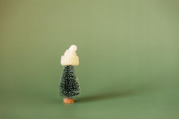 Petit sapin de noël dans une casquette sur fond vert. minimalisme de noël et nouvel an