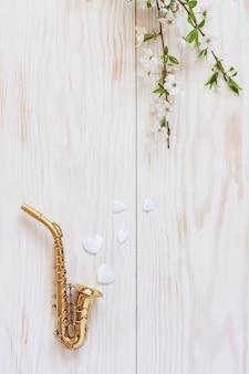 Petit saxophone doré, figurines en forme de cœur blanc et branches de cerisier en fleurs.