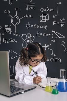 Petit scientifique étudiant et prenant des notes