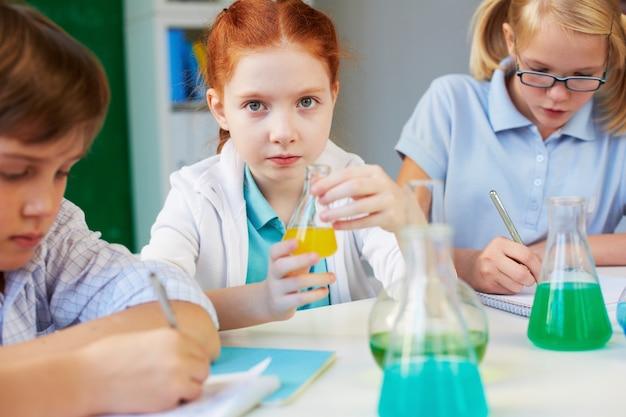 Petit scientifique jouant avec un liquide jaune