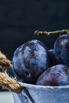 Petit seau de prunes fraîches sur fond noir.