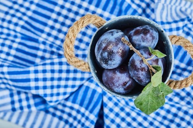 Petit seau de prunes de jardin sur nappe bleue.