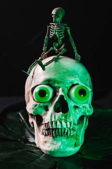Petit squelette assis sur un crâne illuminé