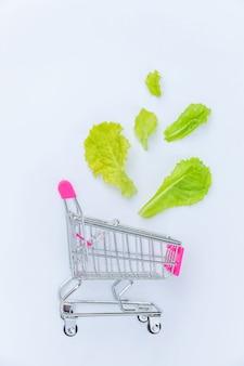 Petit supermarché épicerie pousser panier pour faire du shopping avec des feuilles de laitue verte isolé