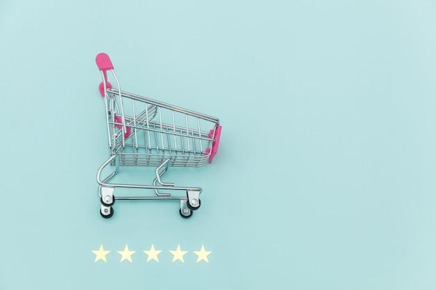Petit supermarché épicerie pousser panier pour faire du shopping jouet avec roues et 5 étoiles classement isolé sur fond bleu pastel. consommateur de détail achetant un concept d'évaluation et d'examen en ligne.