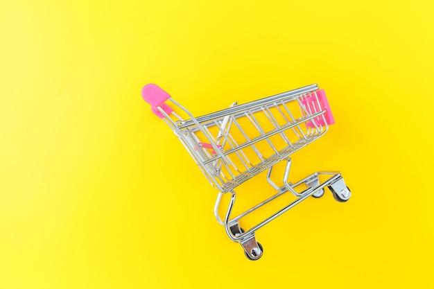 Petit supermarché épicerie pousser panier pour faire du shopping jouet avec roues isolé sur fond de mode moderne tendance coloré jaune. vente acheter centre commercial marché consommateur concept. copiez l'espace.