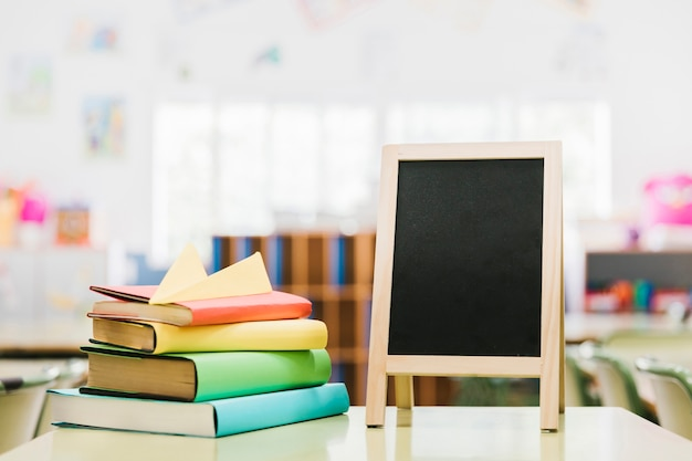 Petit tableau à craie et livres sur le bureau