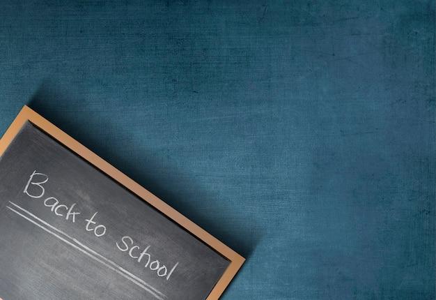 Petit tableau noir avec le texte de la rentrée scolaire sur fond de mur bleu
