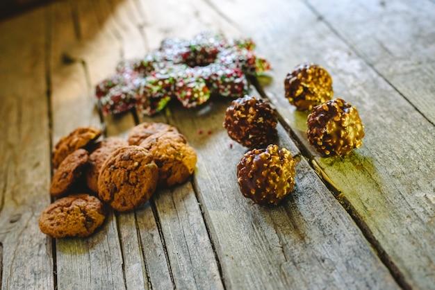 Petit tas de biscuits au chocolat sur des planches en bois vieillies, des bonbons de noël et des chocolats au chocolat à la noisette.