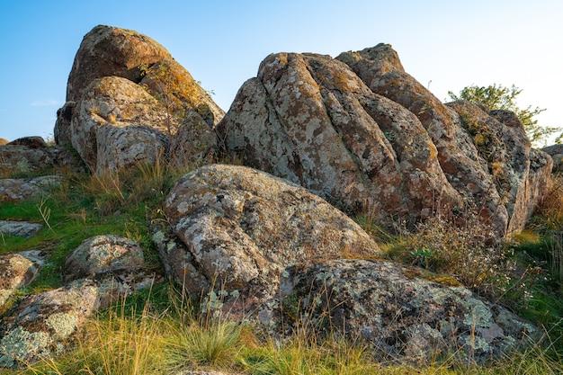 Un petit tas de pierres dans un champ vert-jaune sur fond de ciel en ukraine