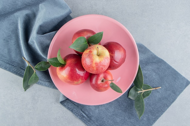 Petit tas de pommes sur un plateau sur un morceau de tissu sur marbre.