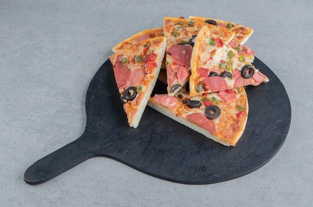 Un petit tas de tranches de pizza sur un tableau noir sur marbre