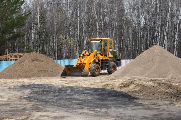 Un petit tracteur avec des outils montés parmi des tas de sable machines de construction
