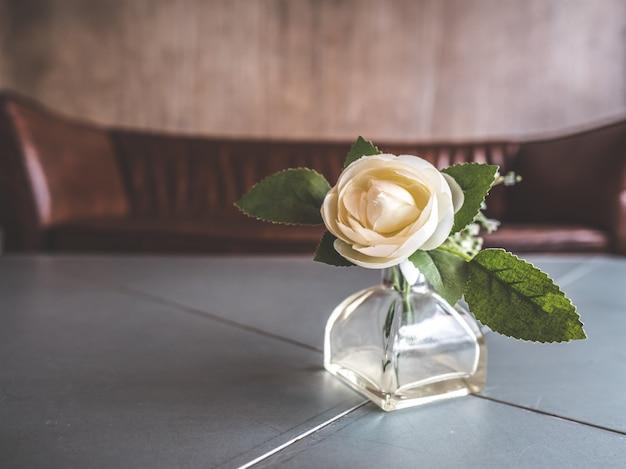 Petit vase en verre avec rose décorative dans la chambre