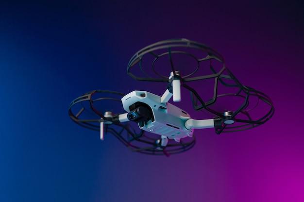 Un petit véhicule aérien sans pilote avec la protection des pales de l'hélice en vol sur fond néon à l'intérieur de la pièce