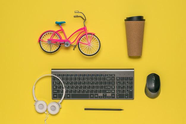Un petit vélo jouet, un verre de café et un clavier sans fil
