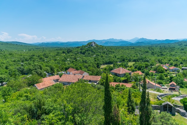 Un petit village est situé dans une plaine au milieu des montagnes.