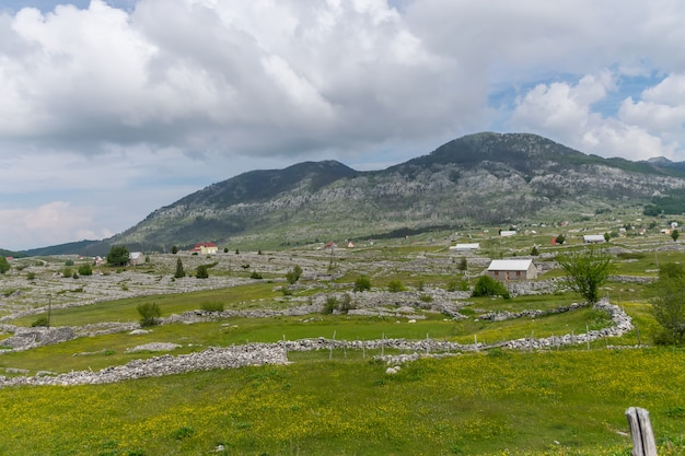 Un petit village est situé parmi de nombreuses collines et montagnes.