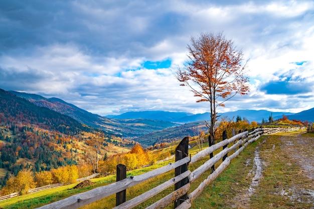 Un petit village sous des collines fantastiques couvertes de forêts colorées d'automne à la lumière d'un soleil chaud et brillant par beau temps