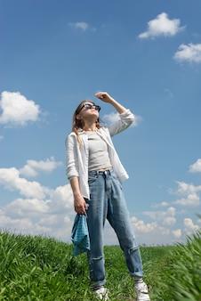 Petite adolescente à lunettes de soleil, dans un champ d'herbe verte, se cachant du soleil, lève les yeux, sur fond de ciel nuageux.