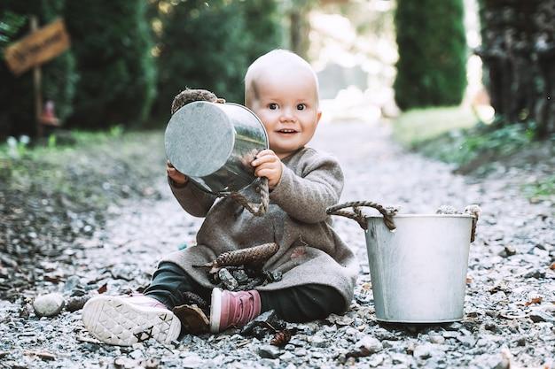 Petite aide de jardinage enfant jouant avec des seaux dans le jardin ou sur la route forestière