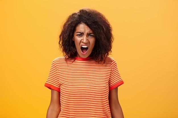 Petite amie afro-américaine aux cheveux bouclés hurlant et faisant une grimace mécontente